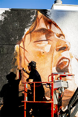 Muralist Robert Vargas works on the Eddie Van Halen mural at Guitar Center Hollywood